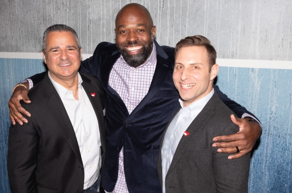 Three men hugging at a party