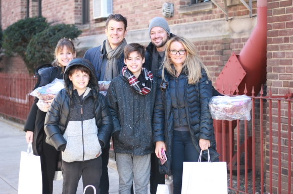 A family holding Thanksgiving delivery bags and holiday baskets