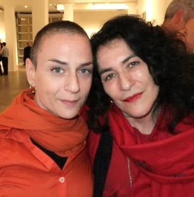 Julie and Janette, both wearing red, with their heads touching