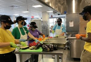 Volunteers in different colored shirts chopping vegetables around a steel table