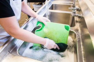 Photo of volunteer in the God's Love kitchen washing a green cutting board.