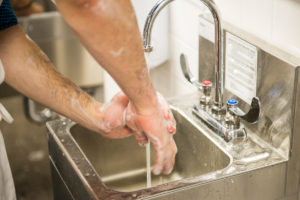 Photo of volunteer in the God's Love kitchen washing their hands.