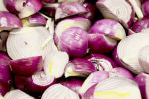 Photo of halved red onions.